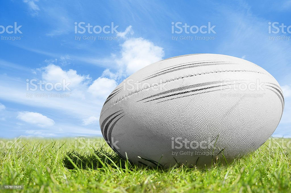 White rugby ball on green grass under blue sky stock photo