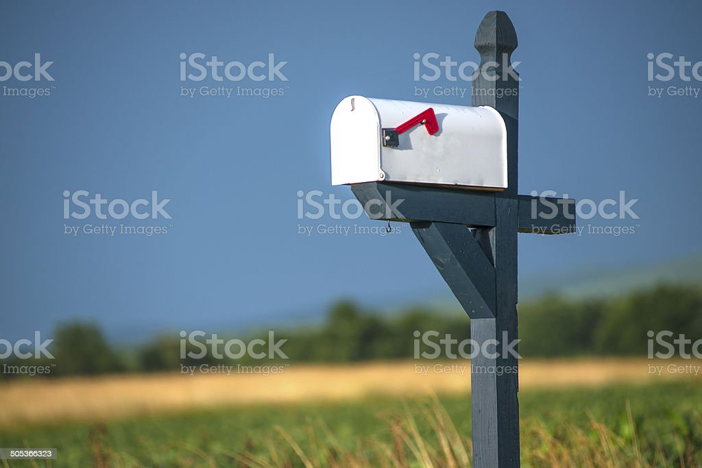 White Rural Mailbox with Red Flag on Blue Post stock photo