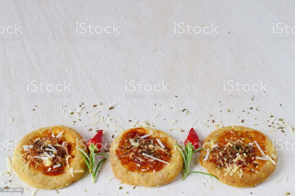 White rustic background with homemade biscuit in a form of pizza with chili, rosemary and spices. Space for text stock photo