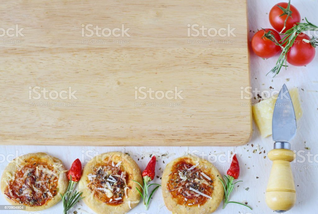 White rustic background with wooden cutting board, homemade biscuit in a form of pizza with chili,rosemary, cherry tomatoes, parmezan, cheese knife and spices. Space for text stock photo