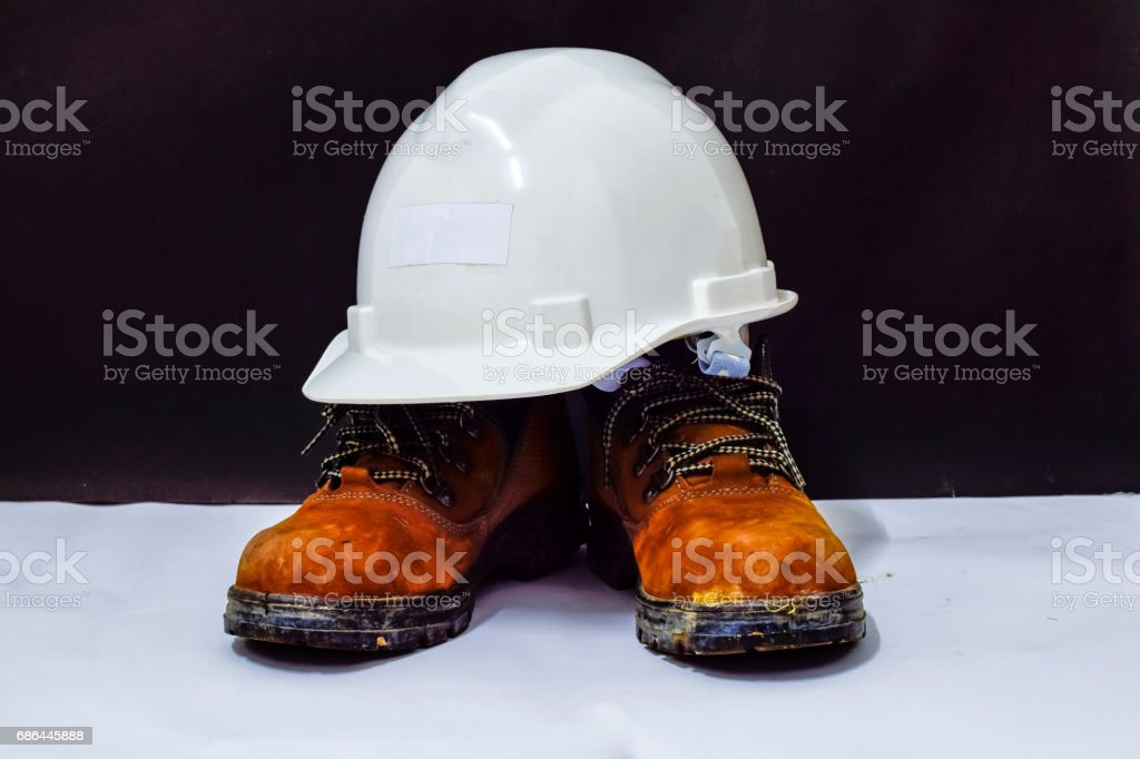 White safety helmet and safety shoes. This is Personal protective...