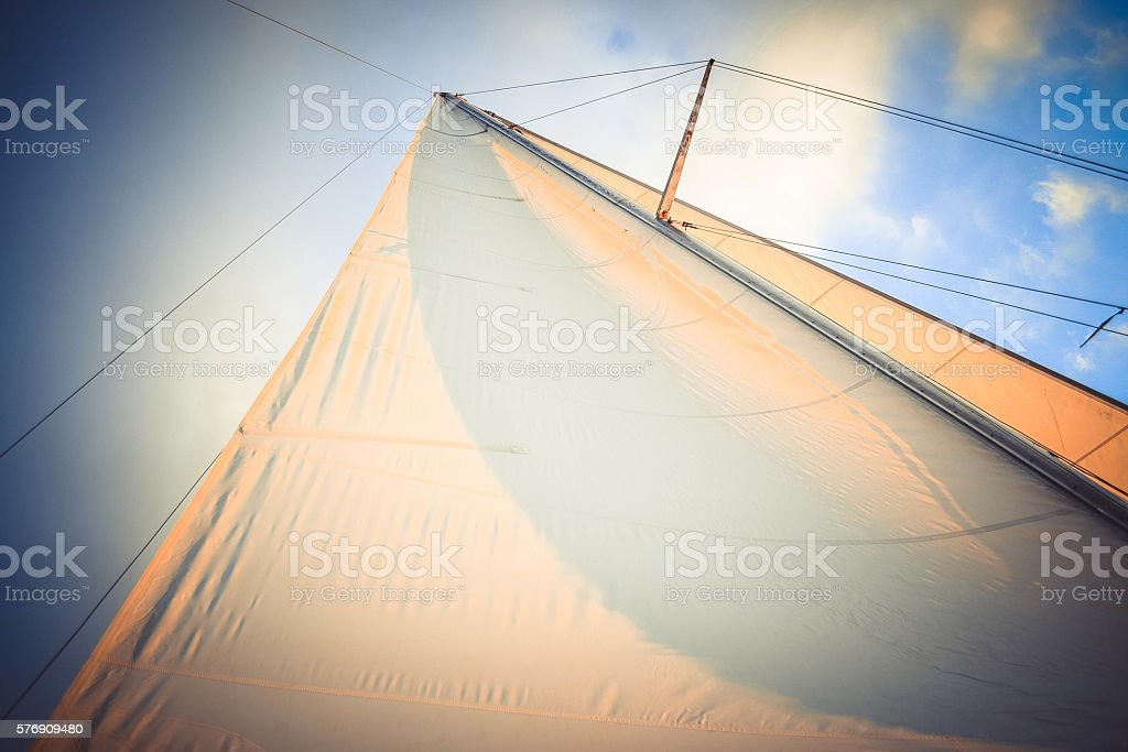 white sail at sunset on a background of blue sky stock photo