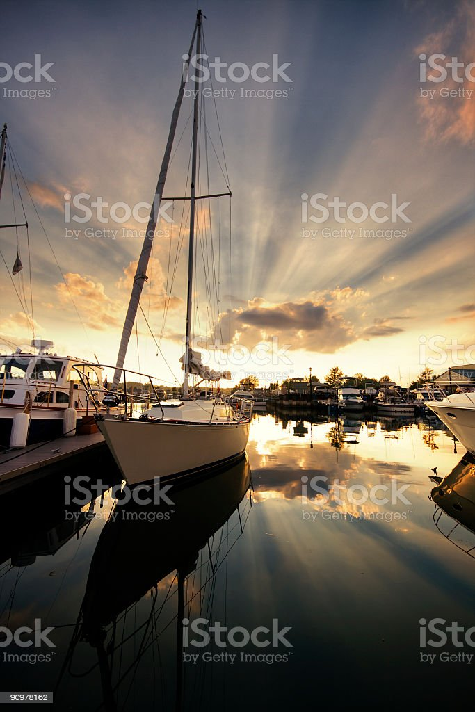 A white sailboat docked at sunset royalty-free stock photo