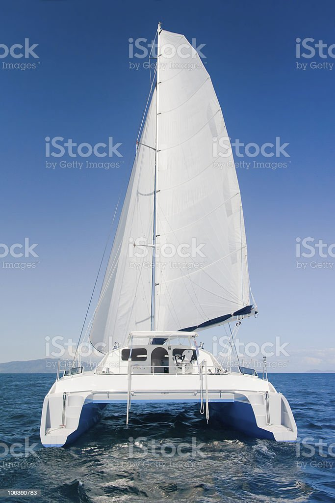 White sailed catamaran on a blue ocean stock photo