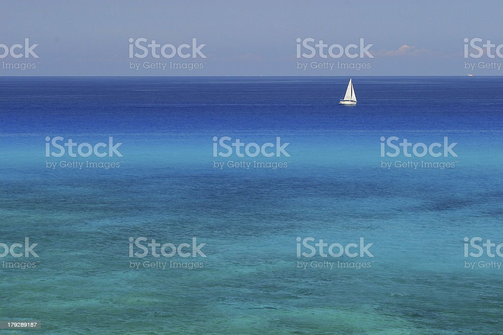 White sailing boat in front of a coral reef royalty-free stock photo
