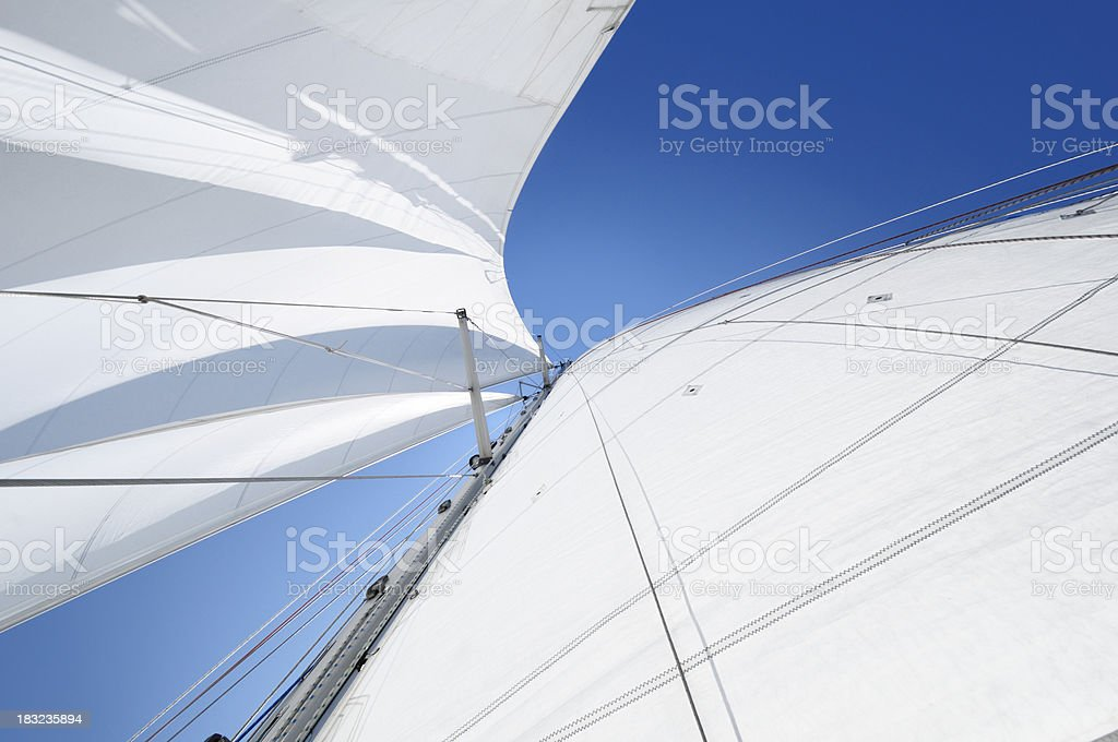 White sails against blue sky seen from below stock photo