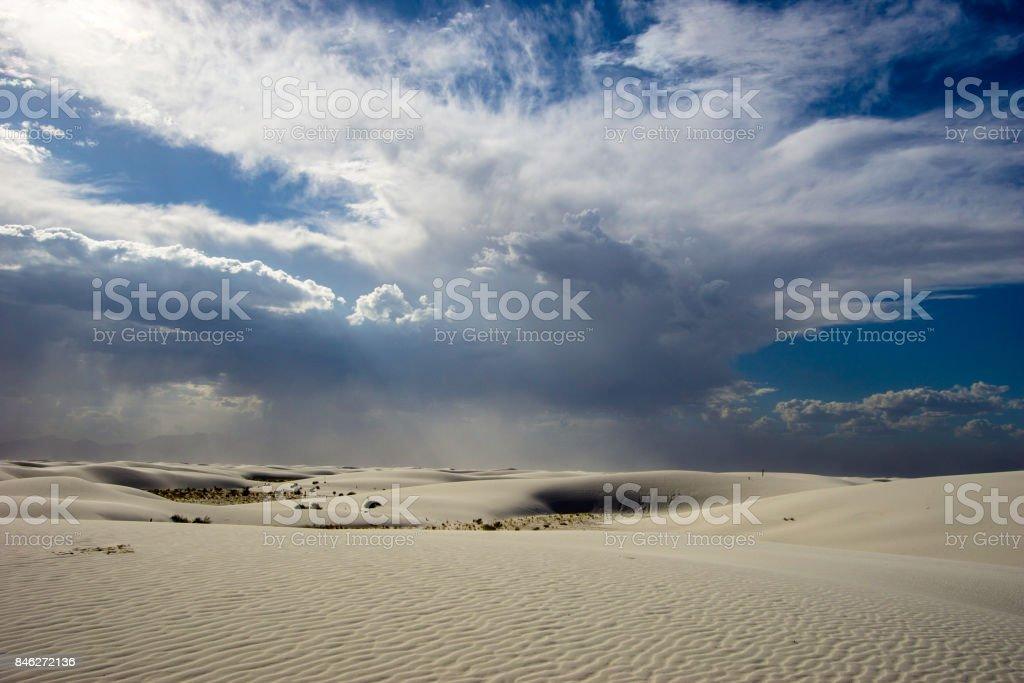 white sand desert under a cloudy sky stock photo