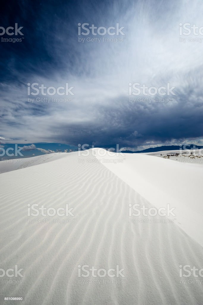 white sand dune in New Mexico under a stormy sky stock photo