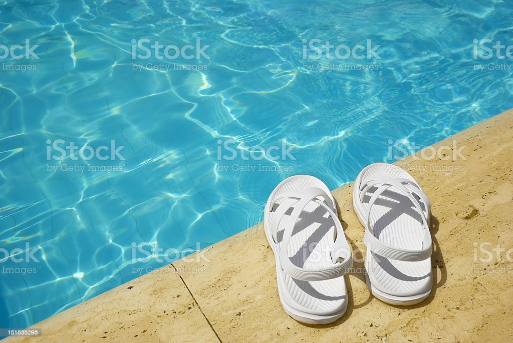 White sandals at the poolside royalty-free stock photo
