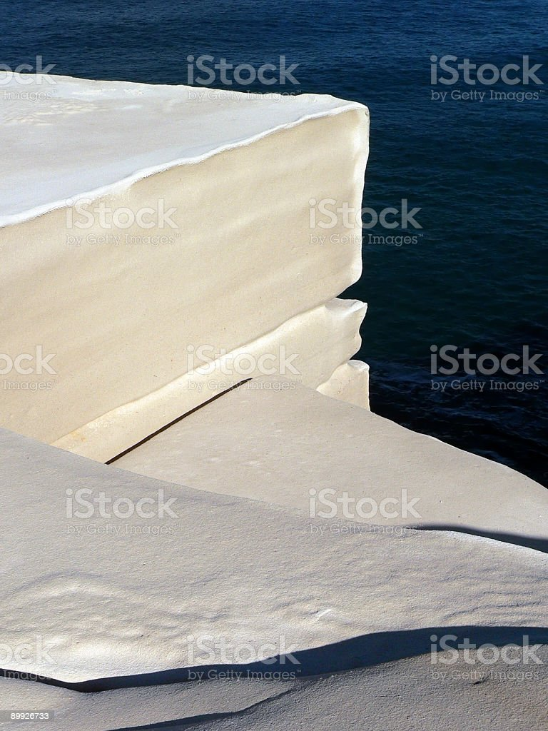 White sandstone cliff Face with dark blue sea in background stock photo