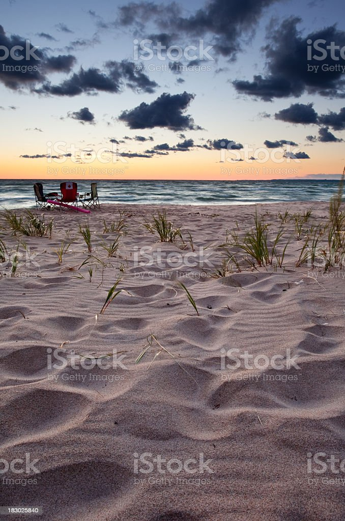 White sandy beach and calm ocean waves at sunset royalty-free stock photo