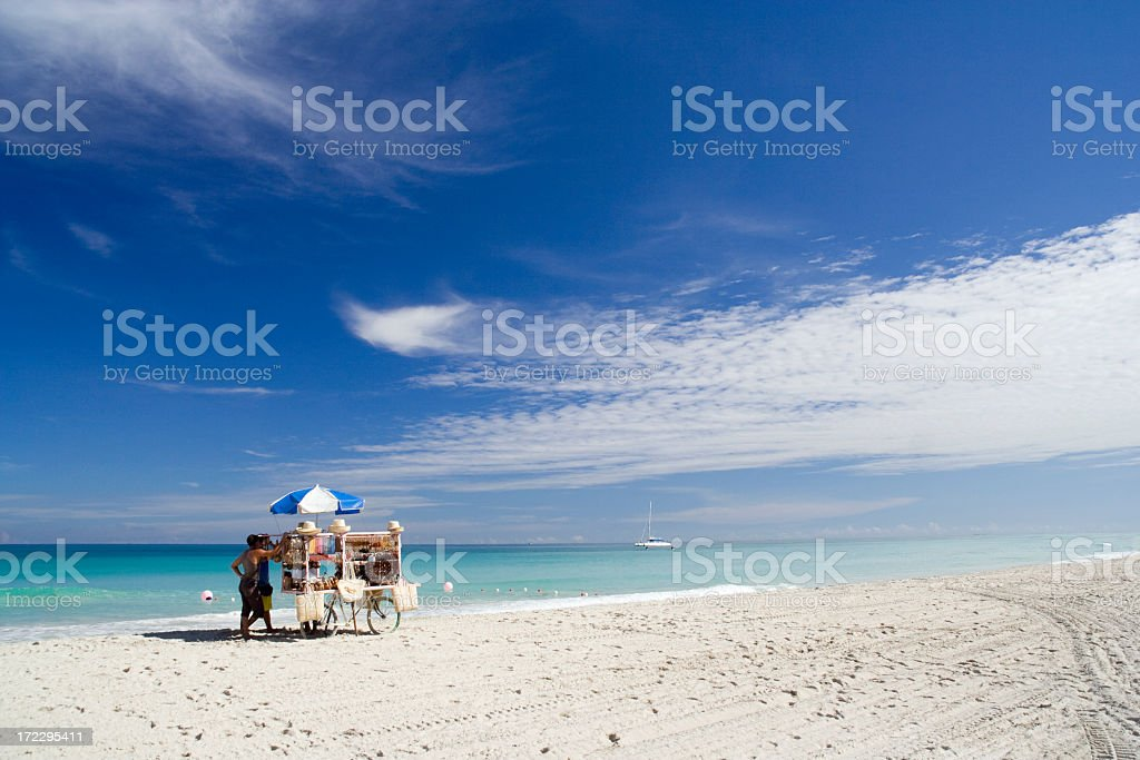 White sandy beach with a merchants cart and umbrella stock photo
