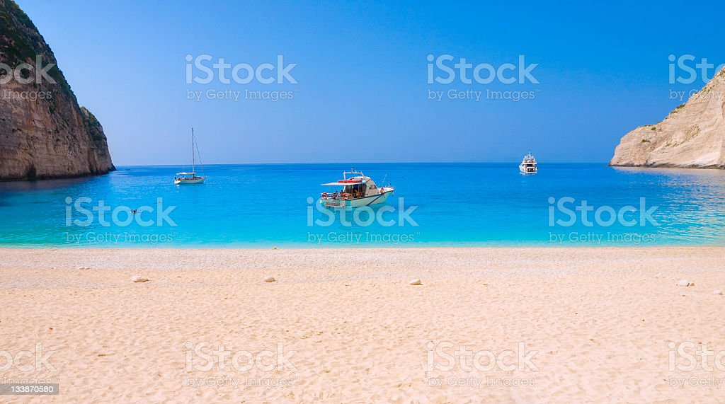 White sandy beach with clear blue sea with three boats royalty-free stock photo
