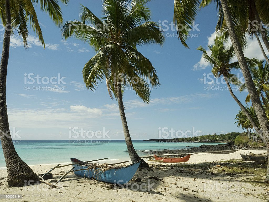 white sandy beach with two fishing boats stock photo
