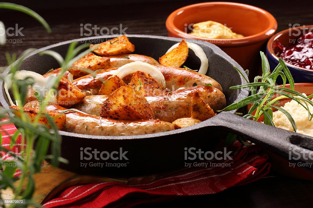 White sausages with potatoes baked in a frying pan stock photo