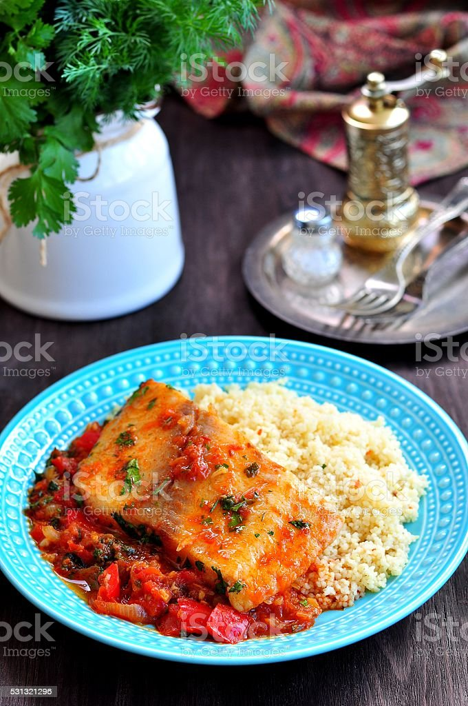 White sea fish cooked in a spicy tomato sauce stock photo