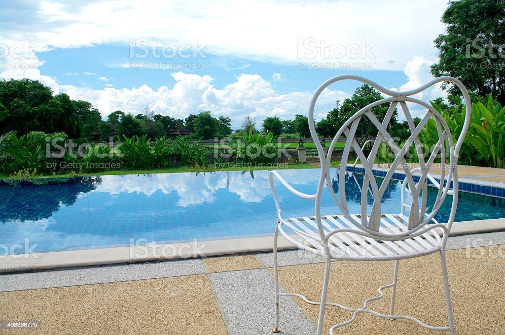 White seat next to swimming pool stock photo