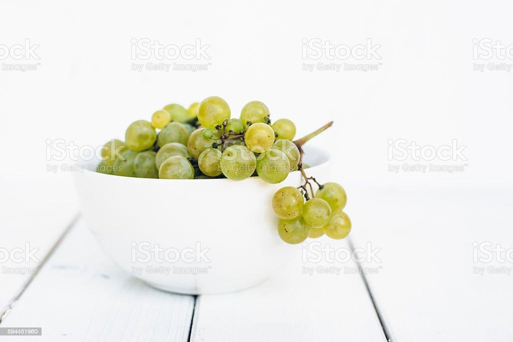 White seedless grapes in white porcelain bowl on wooden table stock photo