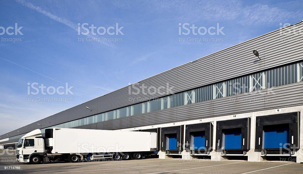 White semi truck backing into a row of loading docks stock photo