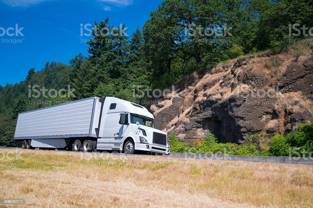 White semi truck trailer going highway with rocks green trees stock photo