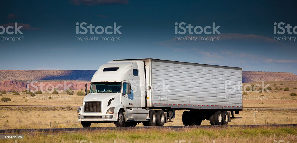 White semi-truck on a word in the desert stock photo