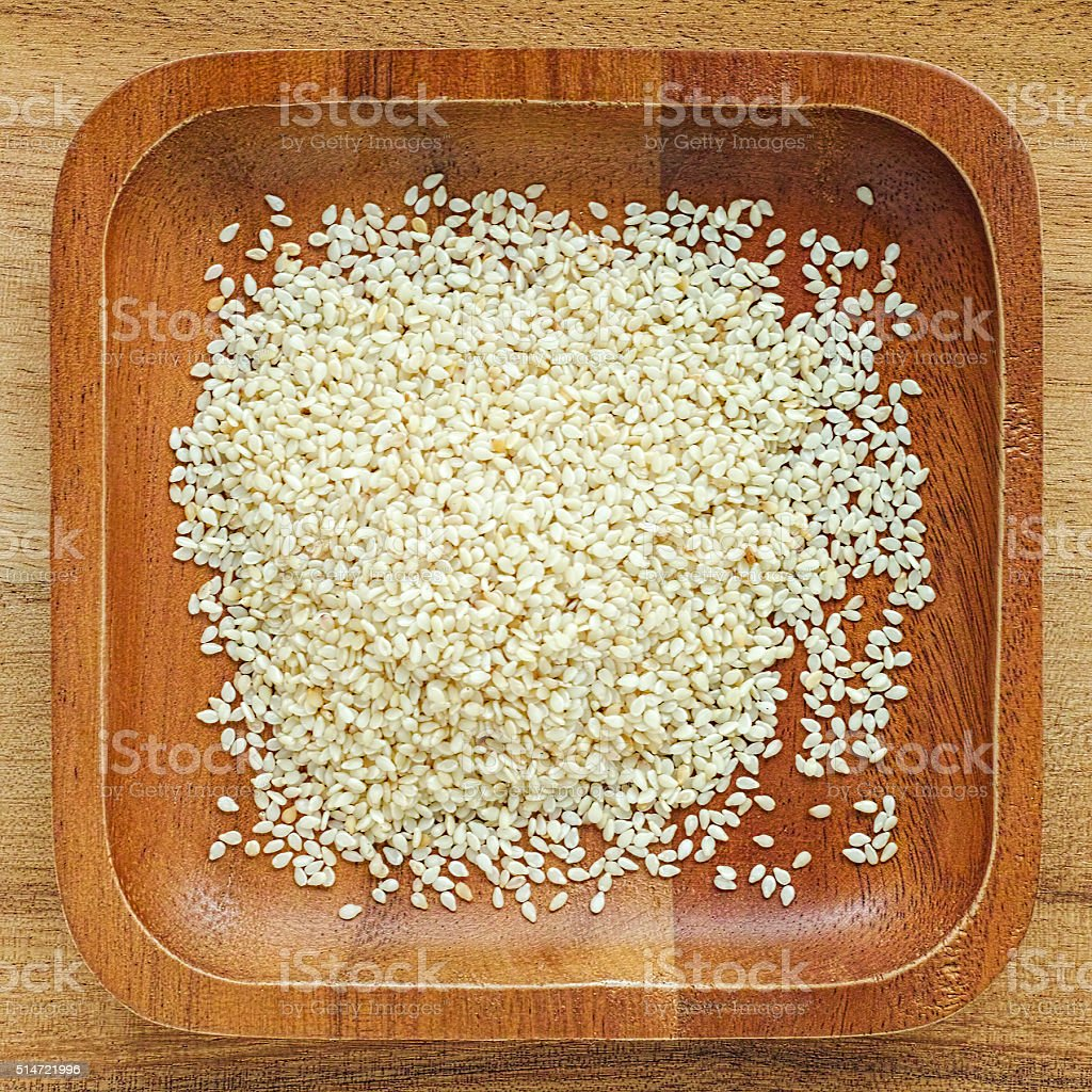 White sesame seeds in a wooden tray. stock photo