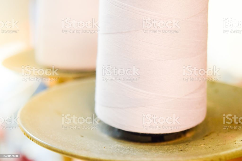 white sewing thread on sewing machine stock photo