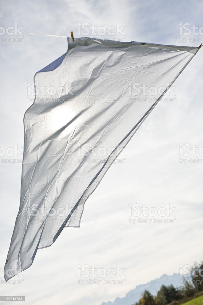 A white sheet hanging from a clothesline stock photo
