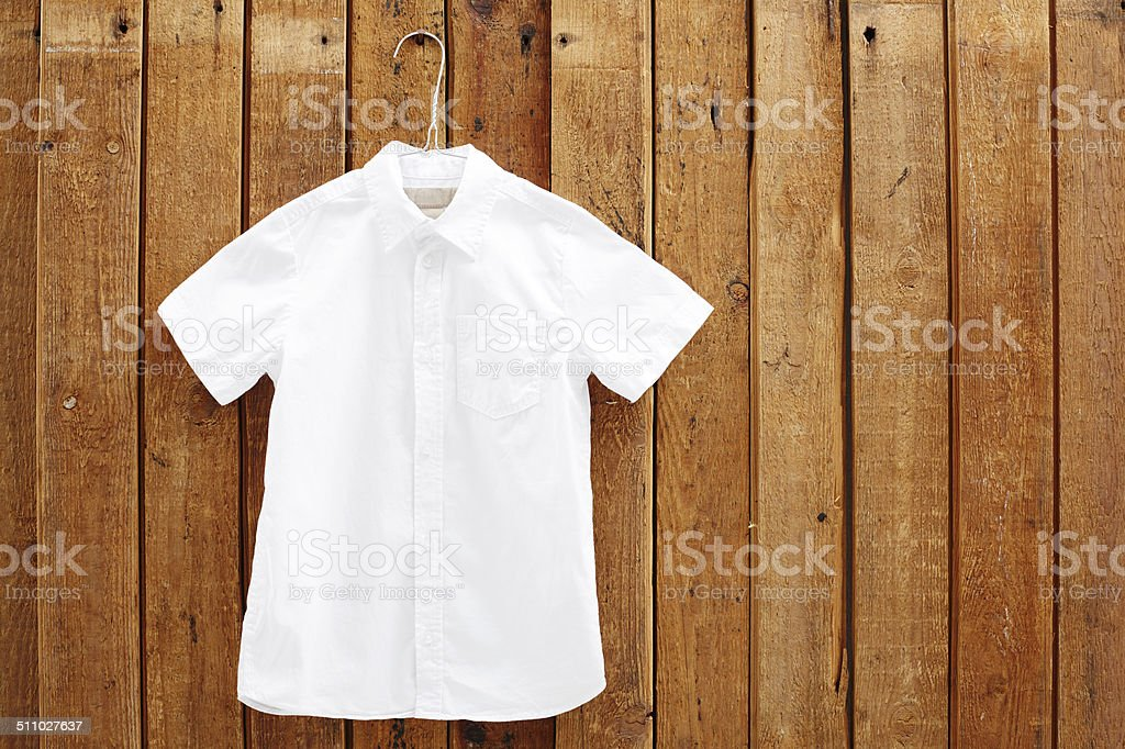White short sleeved shirt hanging against wooden wall stock photo