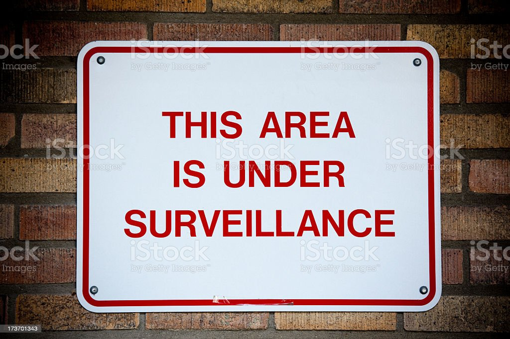 White sign with red writing stating area under surveillance royalty-free stock photo