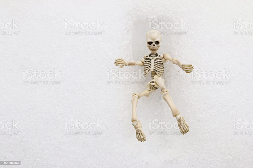 White skeleton trying to get out of a square grave stock photo