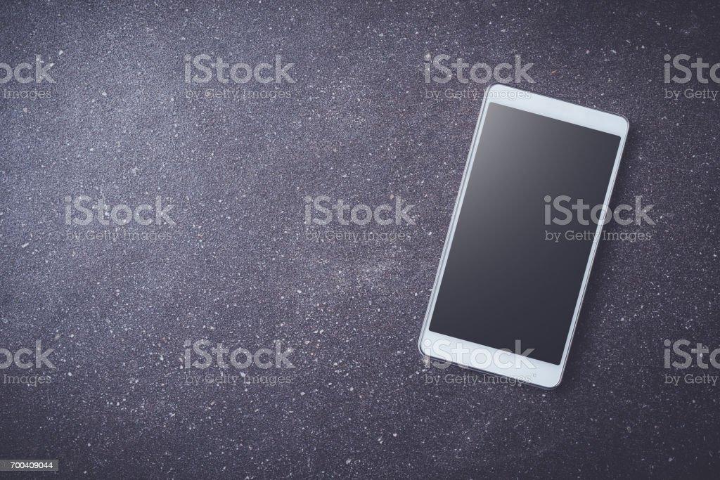 White smart phone on dark stone table stock photo