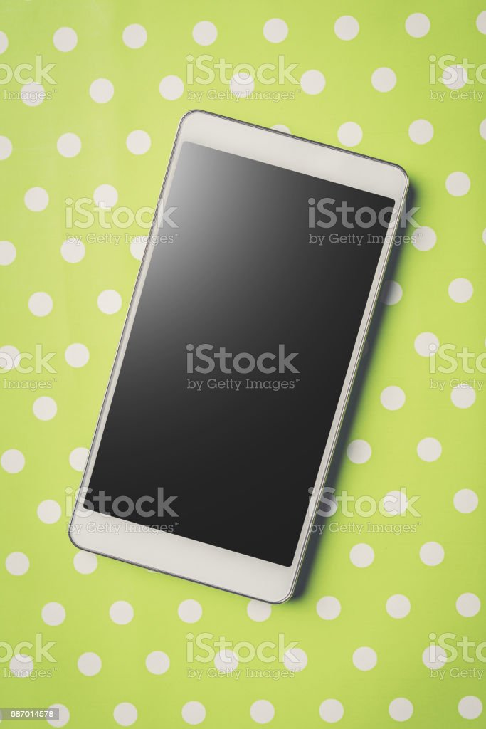 White smart phone on green dotted background. stock photo
