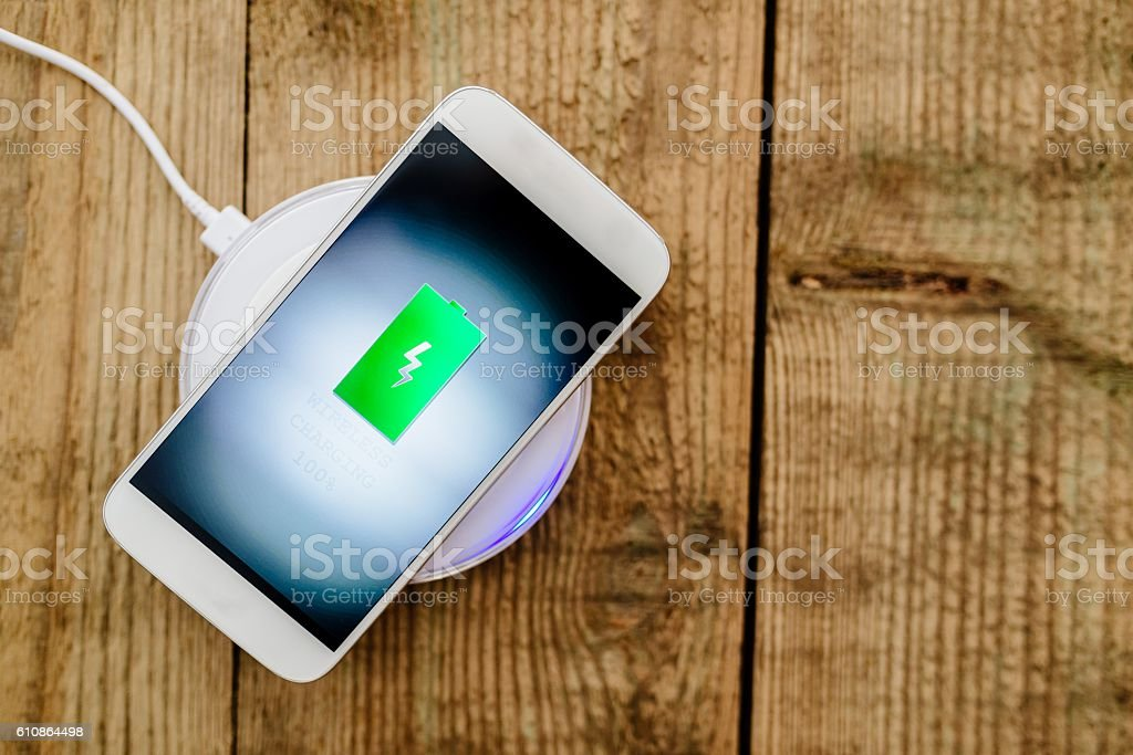White smartphone charging on a charging pad. stock photo