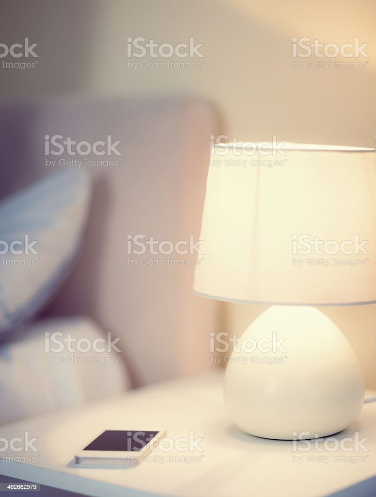 White smartphone lying on a bedside table stock photo