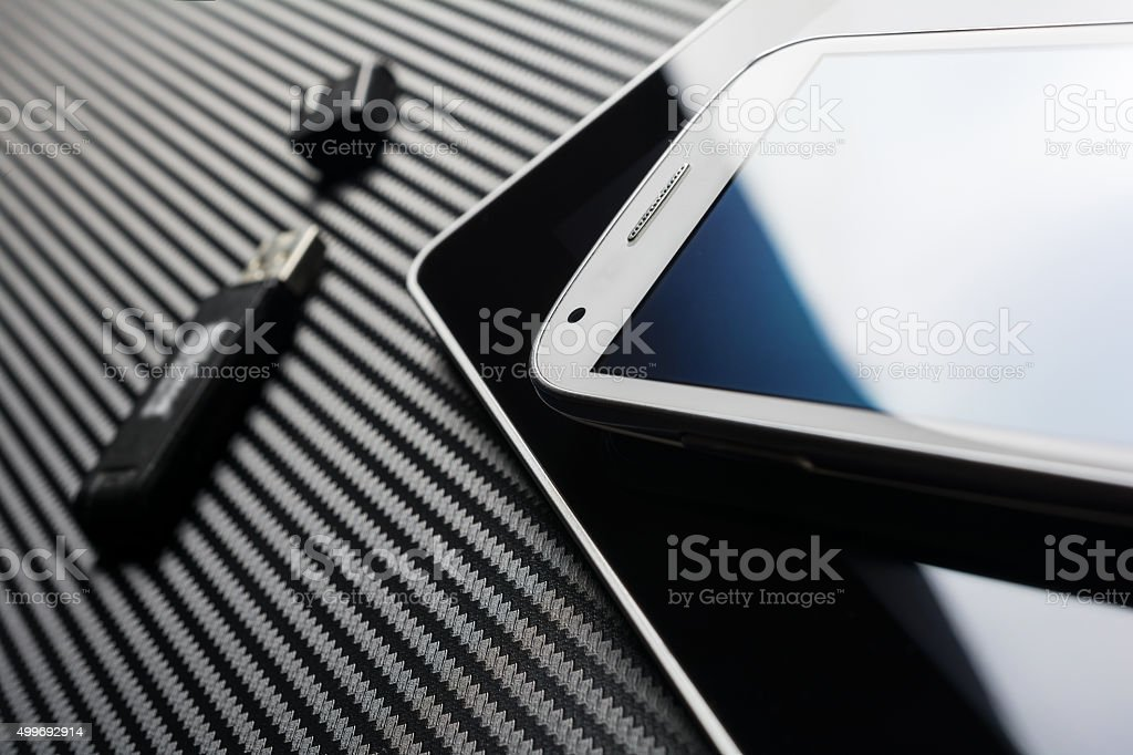 White Smartphone On Tablet Next To USB Drive On Carbon stock photo