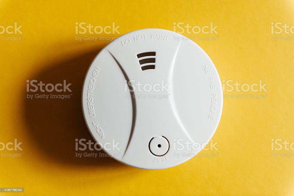 White smoke detector on yellow ceiling stock photo
