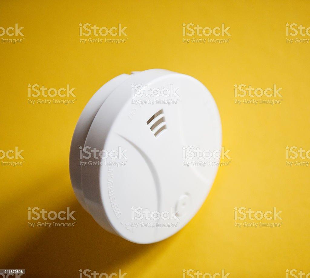 White smoke detector on yellow table. stock photo