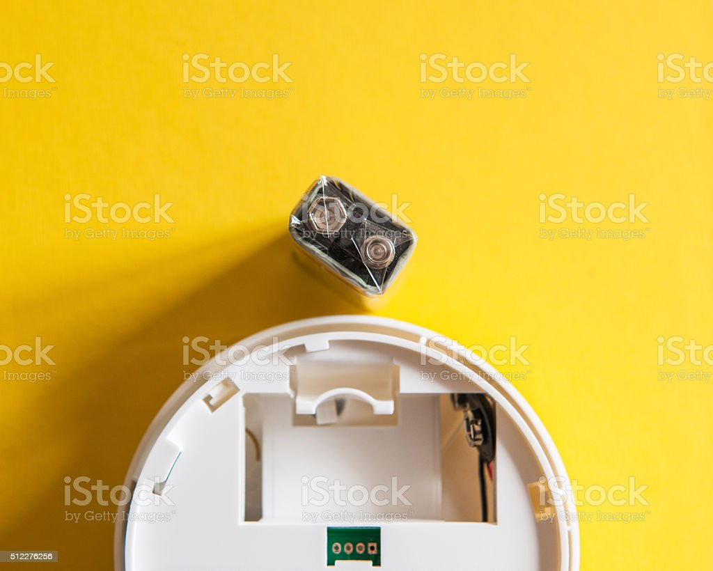 White smoke detector with nine volt battery stock photo
