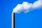 White smoke from a chimney against a bright blue sky