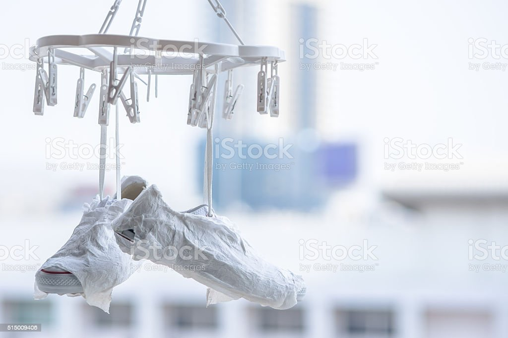 white sneakers hanging on the clothesline stock photo