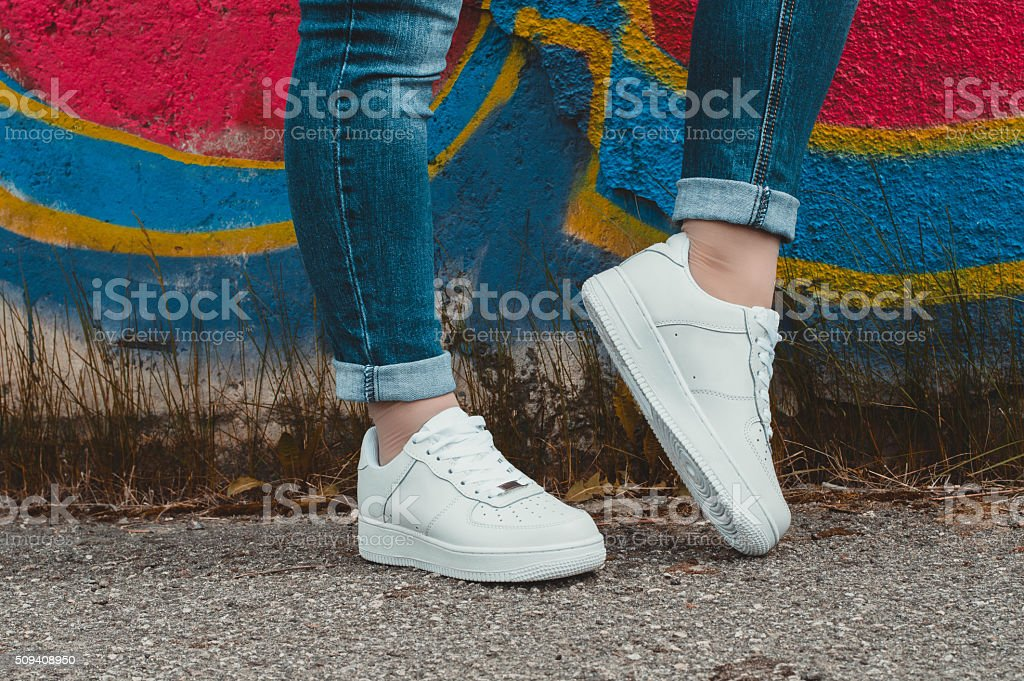 White sneakers on girl legs on the graffiti background stock photo