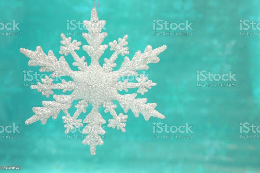 White Snowflake Ornament on an Aqua Turqouise background stock photo