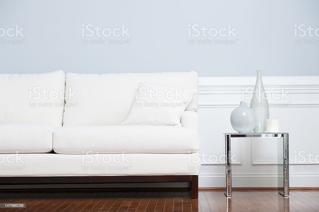 White Sofa and Glass End Table Against Blue Wall stock photo