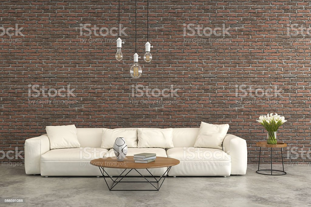 White sofa in front of a brick wall stock photo