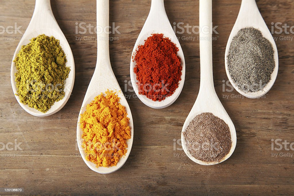 White spoons filled with spices on a wood surface stock photo