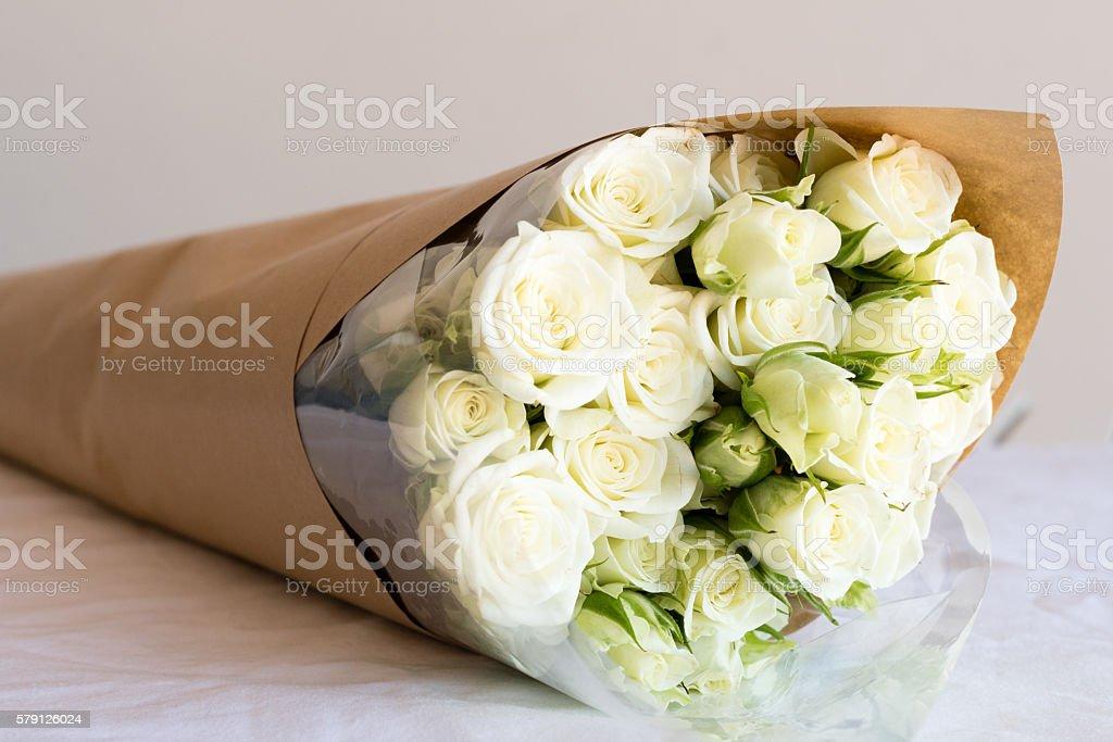 White spray roses in brown paper stock photo