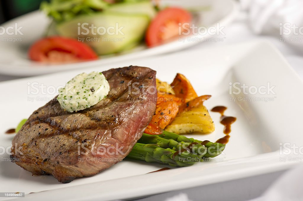 A white square plate containing grilled steak and salad stock photo