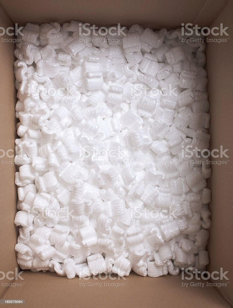 White styrofoam peanuts packed inside of open cardboard box stock photo