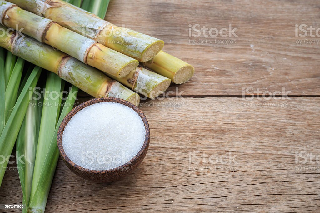 White sugar and sugar cane and leaf on wooden stock photo